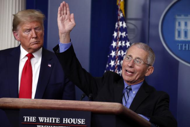 美國傳染病專家佛奇說,估計美國的疫情爆發還要持續數個星期,川普總統在旁注視。(美聯社)