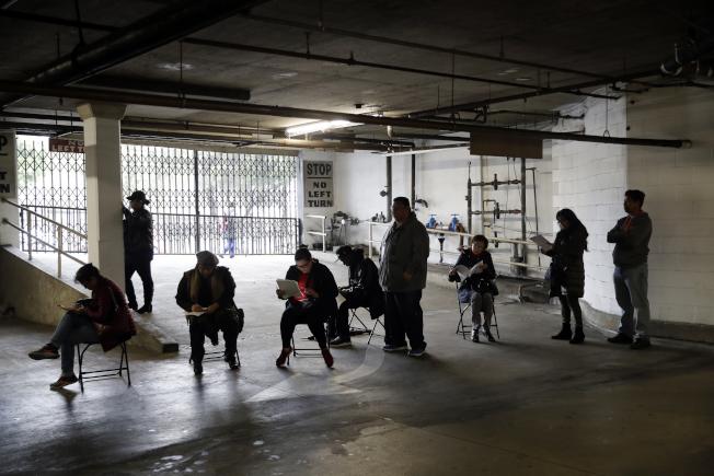 由於經濟萎縮,洛杉磯失業者在一家職訓機構地下室排隊,準備申領失業金。(美聯社)