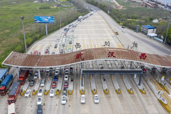 汽車依序通過武漢一處收費站,武漢已解除對大部分區域的出行限制。(新華社)