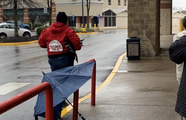 超市員工在雨天借愛心傘給耐心排隊的民眾。(記者張筠 / 攝影)