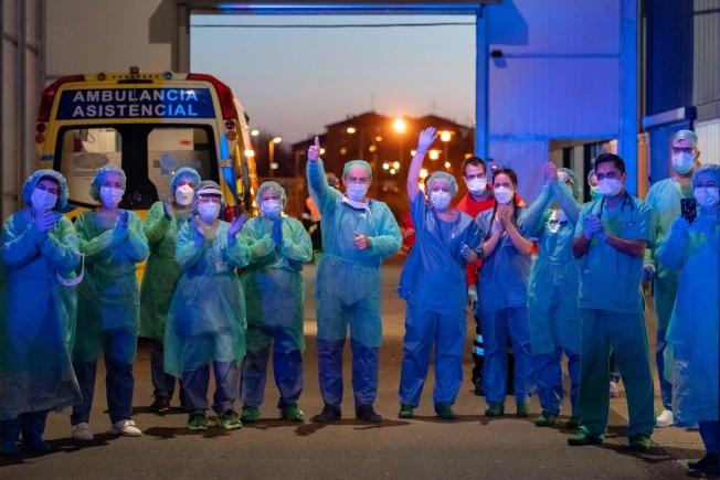 西班牙病例死亡數已超過中國,全球居第二位,但醫護人員仍奮戰不懈。圖為西班牙布爾戈斯居民向醫護人員鼓掌,醫護人員也為自己打氣。(Getty Images)