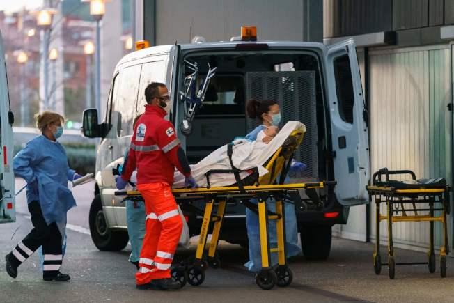 西班牙病例死亡數已超過中國,全球居第二位。圖為救護車把病人送進西班牙布爾戈斯一家醫院搶救。(Getty Images)