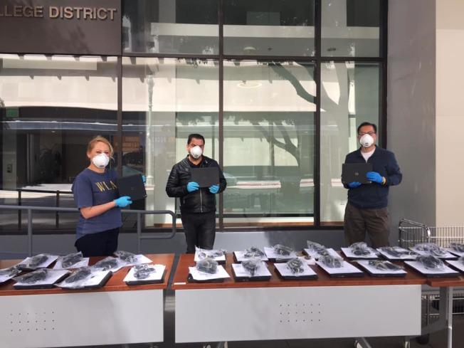 配合洛杉磯社區學院線上教學,方樹強(右一)和工作人員設立分發筆記本電腦攤位。(方樹強提供)