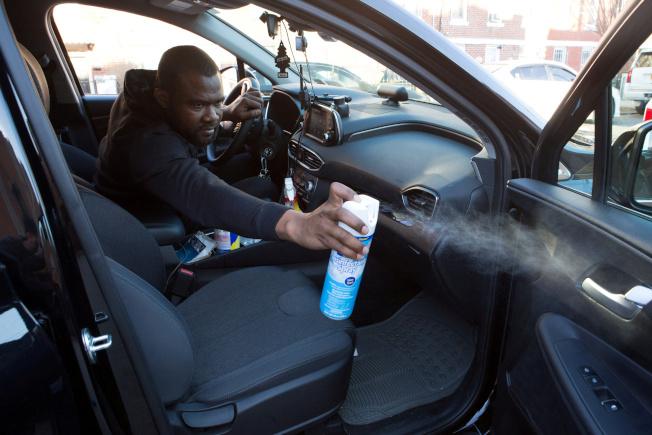 網約車司機嚴防遭受新冠病毒感染,圖為一名優步及Lyft司機為自己的車子消毒。(路透)