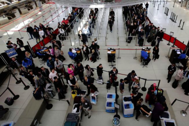 為防堵新冠肺炎病毒,國際機場對旅客進行篩檢。圖為甘迺迪機場旅客排隊。(美聯社)