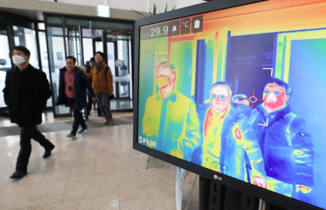各國紛紛防堵新冠病毒疫情延燒。圖為南韓政府大樓用熱像儀監測進出民眾的體溫。(歐新社)
