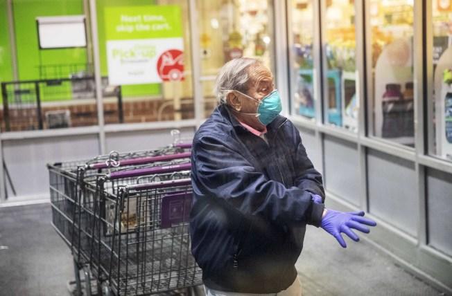 疫情當前,做好準備,一般民眾還是可以安全買菜。圖為一名男子進超市買菜前。戴上口罩和手套。(美聯社)