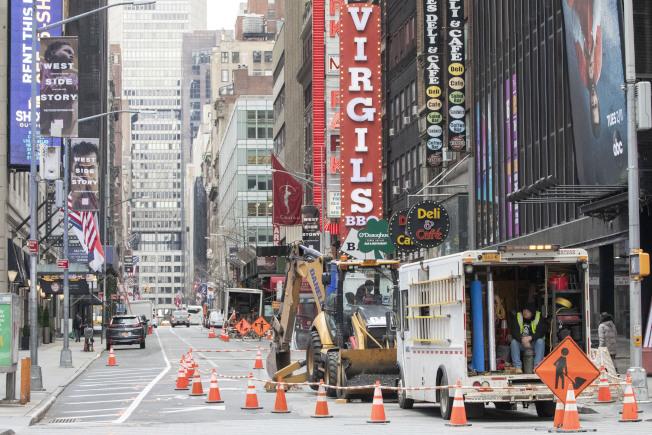 25日,紐約時報廣場,建築工人仍在工作,但街道空空蕩蕩。(美聯社)