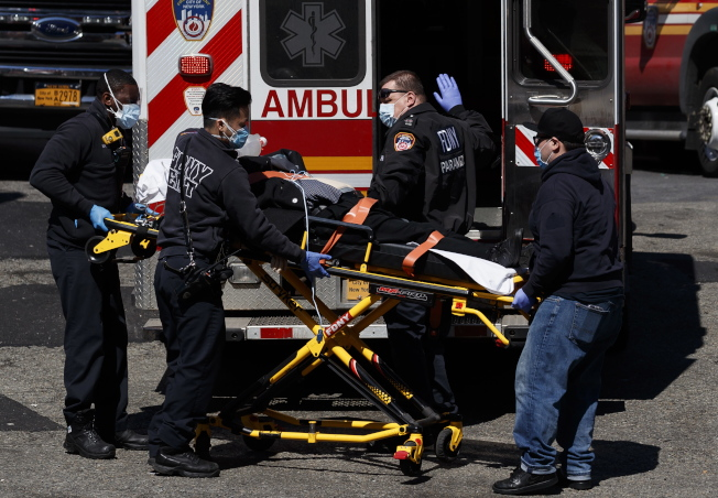 紐約疫情嚴重,皇后區艾姆赫斯特醫院一天內有13名病人去世,圖為救護車將病患送往該醫院在救治。(歐新社)