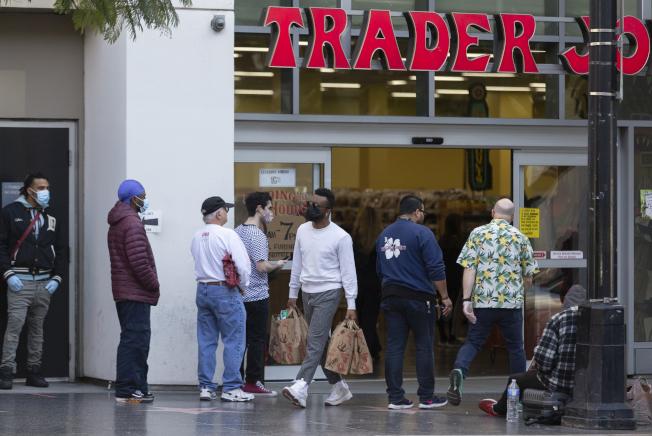 專家說,疫情期間,在人潮擁擠的場合中被別人觸碰到衣物後,就必須更換。圖為洛杉磯一家超市門口的人群。(美聯社)