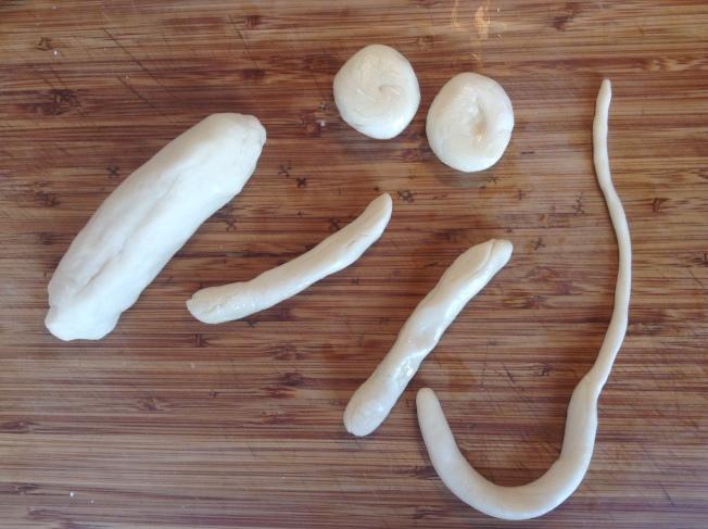 2.像做餃子皮一樣,將麵糰揉勻搓成圓柱後,切成小麵糰,在小麵糰表面抹些植物油後,一隻手拉緊一端慢慢抻長,另一隻手用力擀壓,將麵糰均勻地拉擀成為細長的圓條狀。