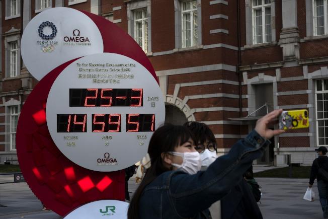 民眾在東京車站前的倒數計時時鐘留影,其已經變成一般的時鐘。(美聯社)