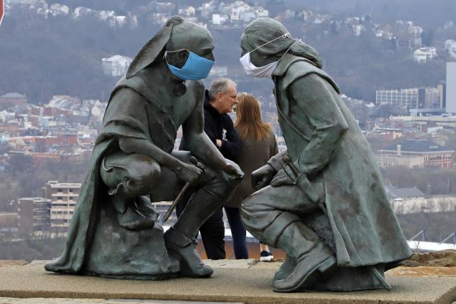 賓州禁止人群集聚,圖為匹茲堡戴上口罩的華盛頓與印第安人雕像。(美聯社)