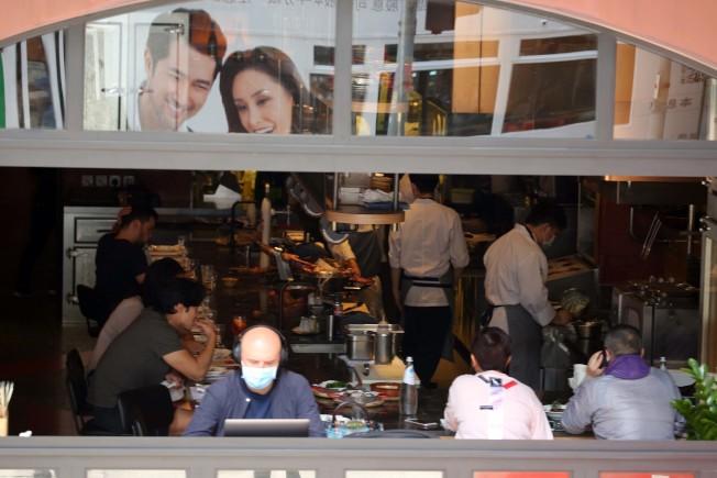 香港政府規定六類場所關閉,進入食肆前要量度體溫,每桌不能多於四人。(中通社)