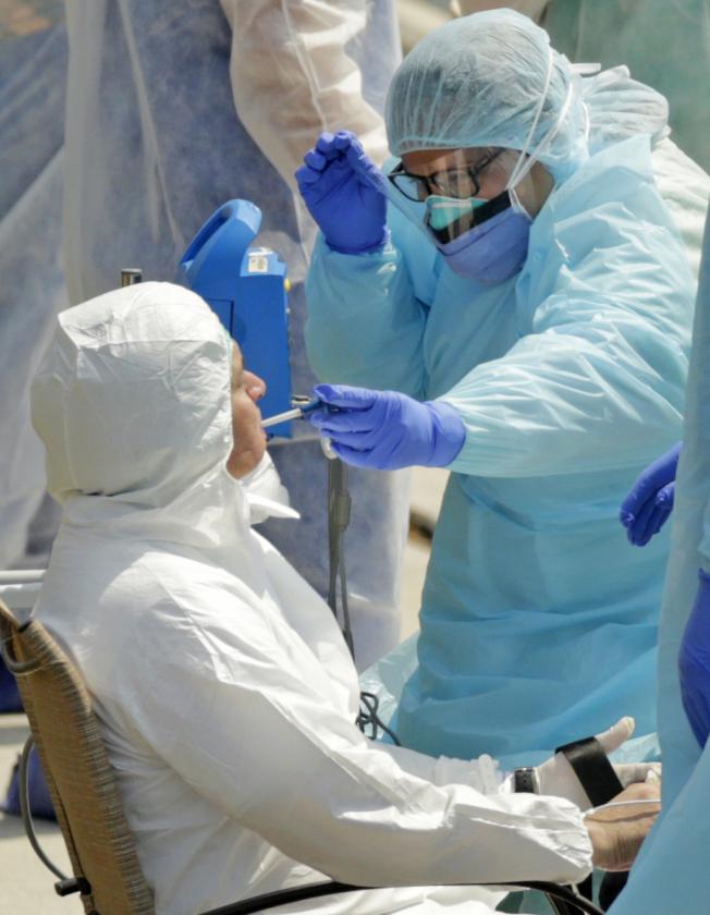 美國確診病例已超過10萬,且爆發成長尚未停止,圖為醫護人員在邁阿密碼頭檢測郵輪上的疑似病例。(美聯社)
