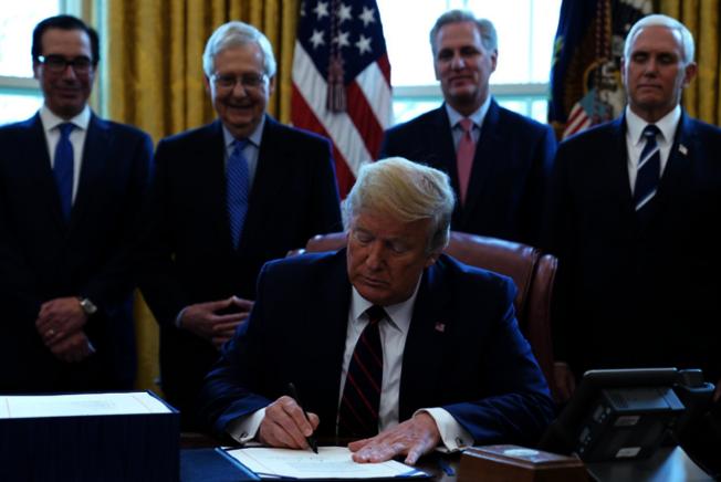 川普總統27日簽署史上最大規模2.2兆元的經濟紓困法案(CARES Act),協助美國民眾和企業擺脫新冠疫情造成的困境。(美聯社)