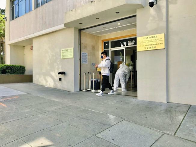 本周五上午11時30分,最後一名完成辦證業務的人士戴著口罩離開辦證大廳,一名身穿防護服的工作人員隨即關門 。(記者黃少華/攝影)