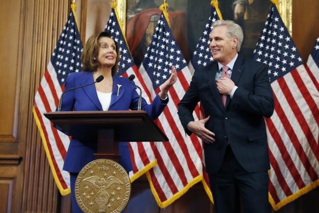 國會眾院迅速通過2.2兆元紓困法案,圖為議長波洛西(左)稱許共和黨籍眾院少數黨領袖麥卡錫充分配合兩黨合作。(美聯社)