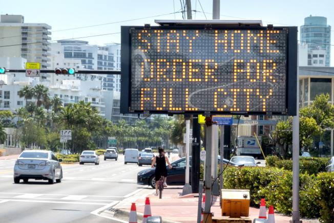 邁阿密實施宵禁,市區道路上提醒民眾,已對全市發出居家令。(歐新社)