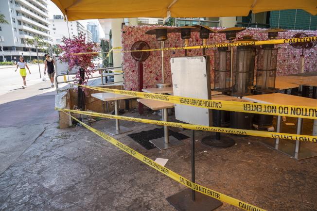 邁阿密實施宵禁,原本熱鬧的南灘餐館乾脆拉閘歇業。(歐新社)