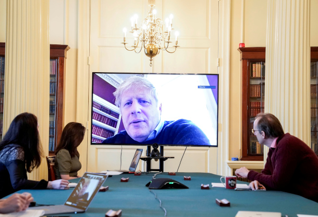 確診在家隔離的英國首相強生,28日遠距視訊參加在倫敦舉行的新冠病毒會議。(路透)