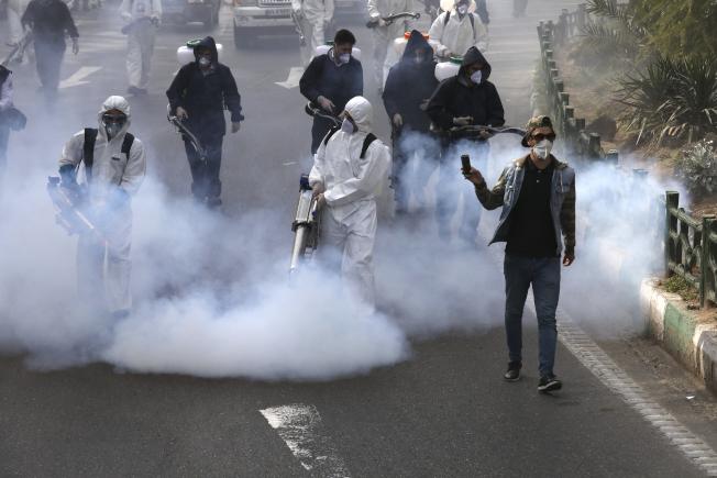 伊朗衛生當局持續在街頭進行消毒。(美聯社)