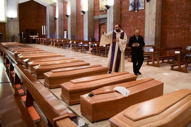 義大利疫情超級慘重,死亡人數破萬,圖為義大利一座教堂擺滿棺材,神父為正為死者祈禱。(Getty Images)