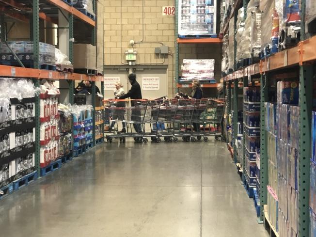 部分限購商品貨架前,工作人員用隔離帶規劃好購物路線。(讀者提供)