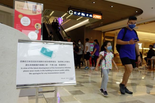 3月28日,香港太平山山頂廣場門口擺放著提醒顧客戴口罩的告示。因應新冠肺炎疫情,香港特區政府出台更加嚴格的防控措施。(中通社)