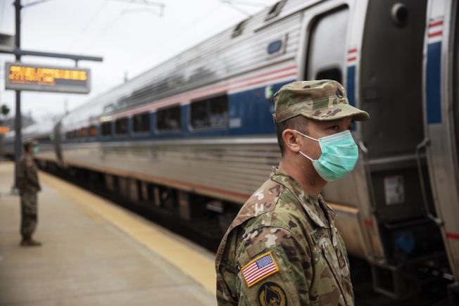 羅德島州國民兵在美鐵車站攔截紐約客,要求他們自行居家隔離。(美聯社)