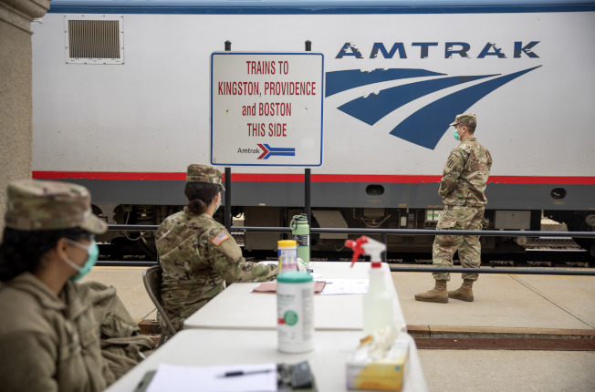 羅德島州國民兵在美鐵車站攔查紐約客,要他們自行居家隔離。(美聯社)