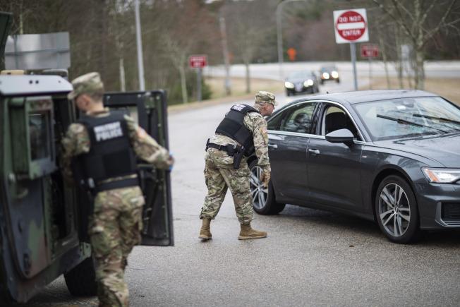 羅德島州國民兵攔查懸掛紐約車牌的汽車,要求他們居家隔離。(美聯社)