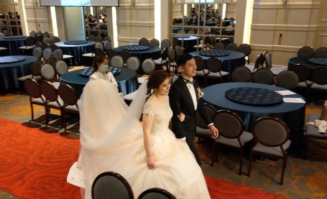 中央流行疫情指揮中心建議暫停舉辦室內超過100人的活動,婚禮怎麼辦?這對新人把40桌的婚宴減半,並安排在兩個不同的廳,新人與一旁空下來的座位形成強烈對比。(記者林澔一/攝影)