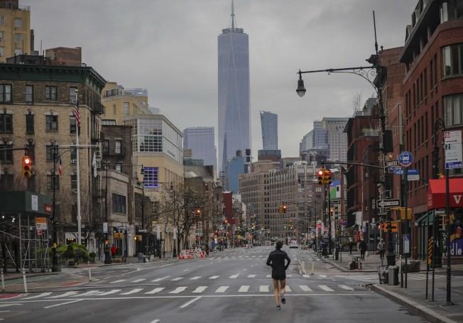 紐約曼哈頓,空蕩的街道上有人在跑步鍛煉。(美聯社)