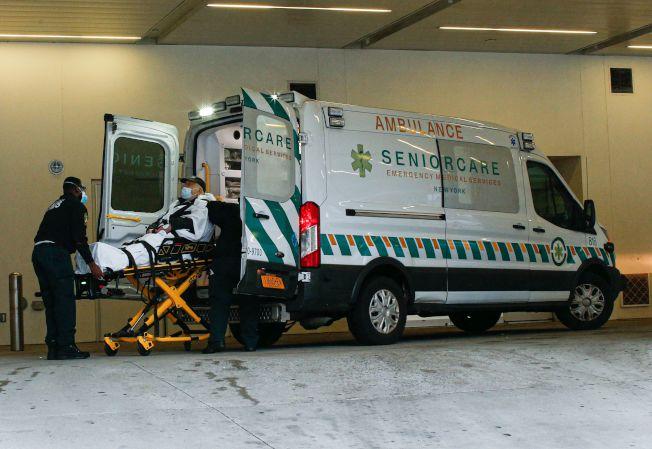 29日,在紐約市,醫護人員正將一名男子運上救護車。(Getty Images)