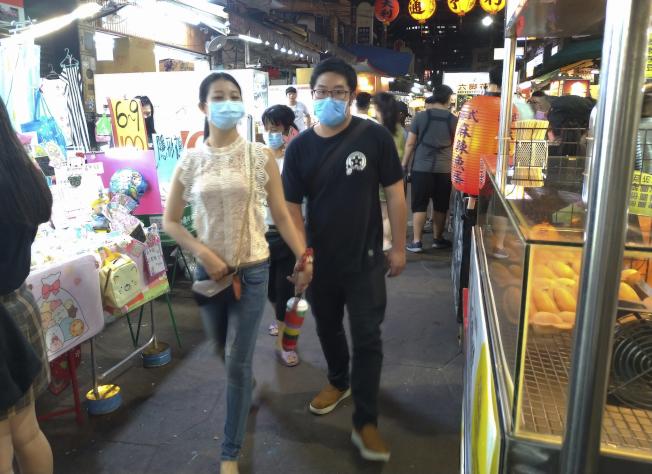 26日,台北一處夜市,民眾戴口罩出行。(美聯社)