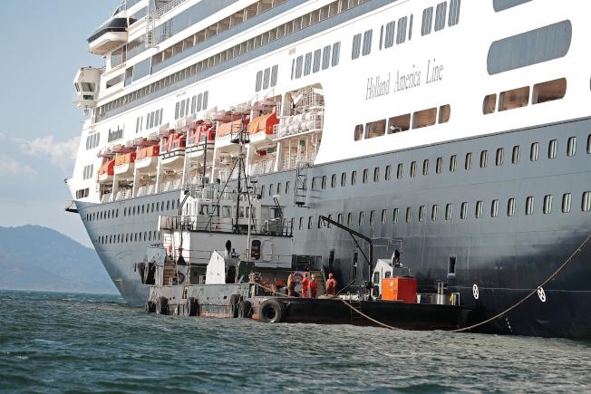 荷蘭郵輪贊丹號滯留在巴拿馬外海,輪上其中部分已感染新型冠狀病毒,29日得知終於可望抵達佛羅里達州,但乘客要換輪。圖為部分乘客正在登上小艇前往另一艘郵輪。(路透)