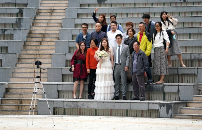 香港實施更嚴厲防疫措施,婚禮上不得多於20人聚集。圖為29日,一對新人和親友參加完婚禮後在香港公園裡拍照留念。(中新社)