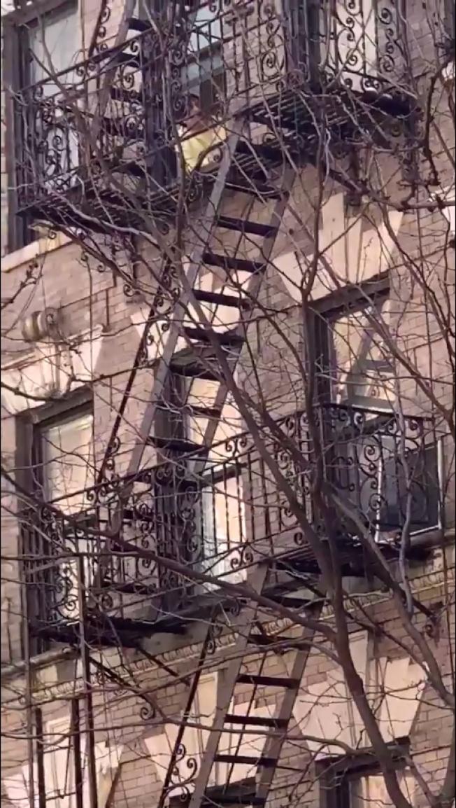 紐約一名男子受不了隔離無聊生活,在窗台對外高歌,結果被人嗆要他「他媽的閉上嘴!」。Twitter/@revoltchild