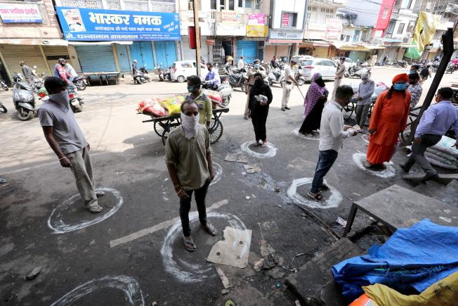 印度中央邦首府博帕爾民眾28日在雜貨店外排隊準備購物時,站在白色園圈內和彼此保持社交距離。(歐新社)