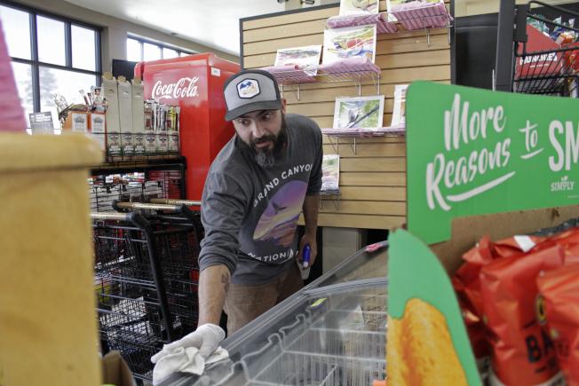 俄勒岡州小鎮市場店家工作人員消毒冰品展示櫃防疫。(美聯社)