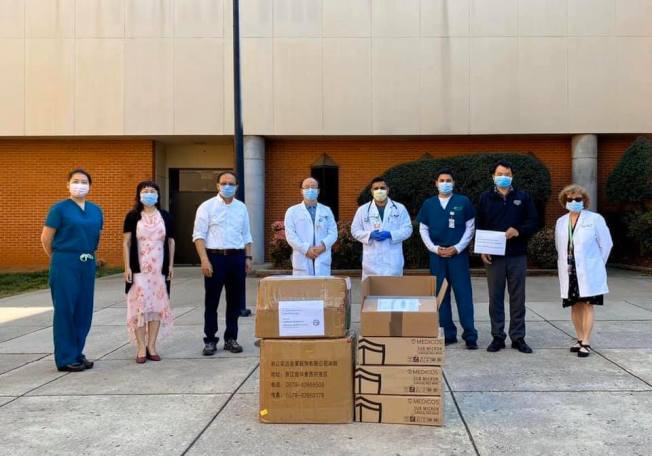 亨城華人協會於日前捐贈了5000個醫用口罩和100套醫護隔離服給亨茨維爾醫院(Huntsville Hospital),右二為 該協會會長林青,左三為亨城阿拉巴馬農工大學孔子學院院長王勇。(亨城華人協會提供)