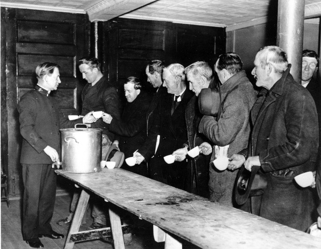 聯準會預測這次新冠疫情將使4700萬人失業,超過「大蕭條」。圖為1929年到1933年時期,失業民眾列隊領取「救世軍」發賑的湯食。(美聯社)