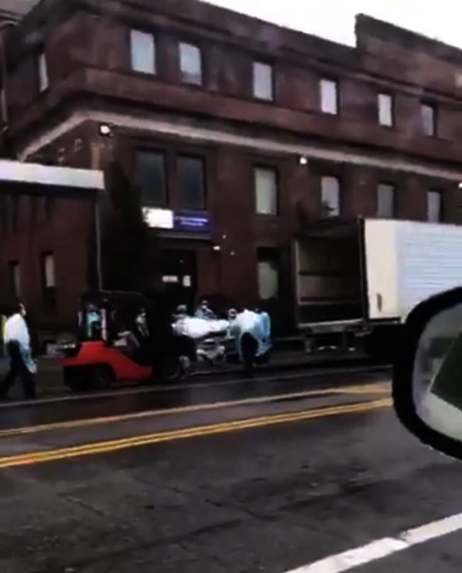 醫院用鏟車將一具具屍體裝在冷藏車中。(視頻截圖)