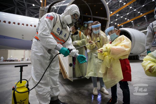 滯留湖北的台灣民眾29日晚間搭乘華航類包機抵台後,國軍化學兵為他們進行消毒。(圖:軍聞社提供)