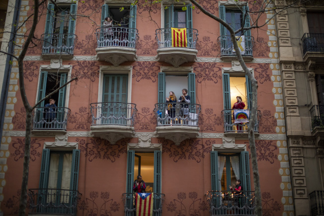 西班牙確診新冠人數超越中國大陸,變成全球第三。圖為西班牙人30日在陽台為醫療人員加油打氣。(美聯社)