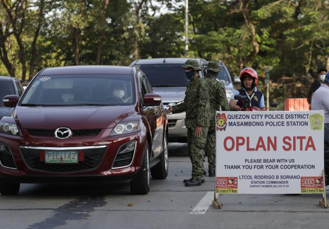 圖為菲律賓警察在首都馬尼拉的一個檢查站攔下汽車進行檢查。美聯社