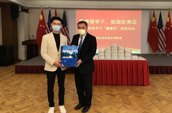中國駐洛杉磯總領事張平(右)向留學生代表發放「健康包」。(中領館提供)