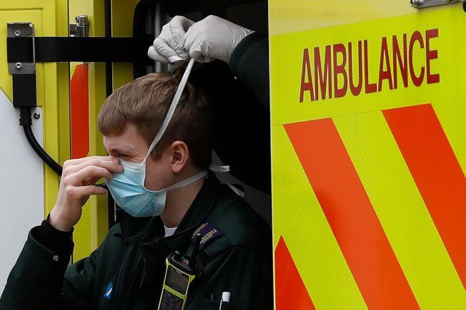 英國醫護人員出動前,由同事幫忙帶口罩。(Getty Images)