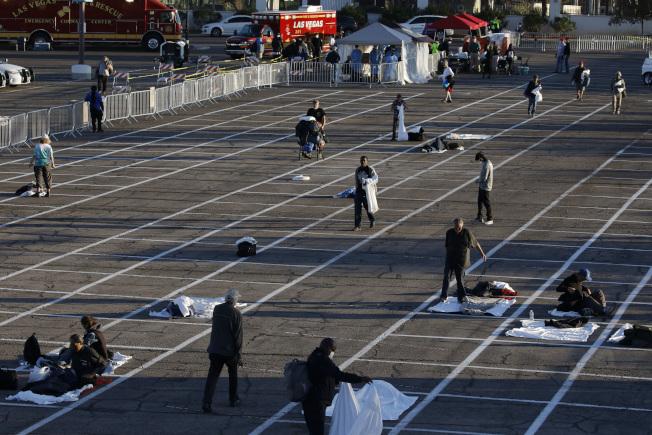 拉斯維加斯近日把停車場改成露天收容站,在地面畫格子,每個相距六呎,集中收留遊民。防止新冠病毒在遊民中擴散。(美聯社)